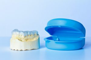 Dental mouth guard on a teeth model next to a plastic storage case