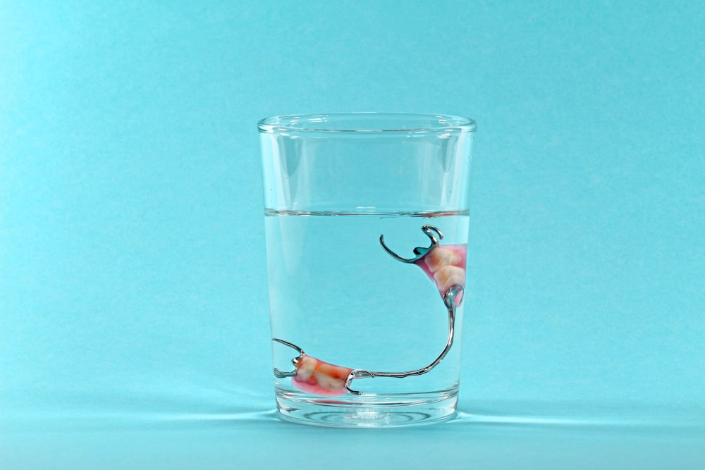 Partial denture soaking in a glass of water against a light blue background